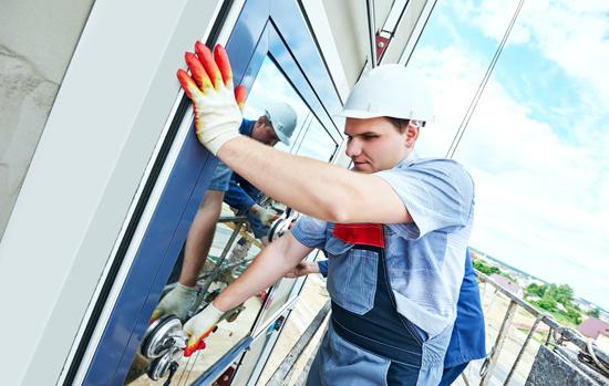 builders worker installing glass windows on facade