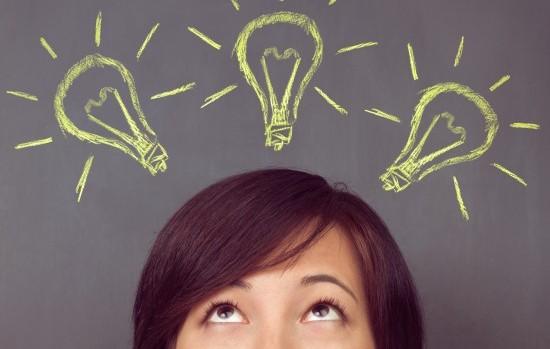 Woman looks up on light bulb