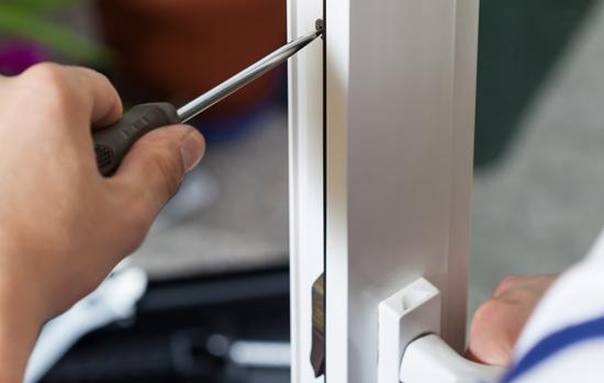 Handyman repairing window with screwdriver