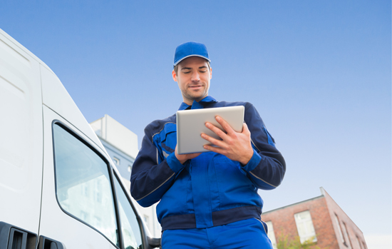 Delivery Man Using Digital Tablet By Truck Against Sky