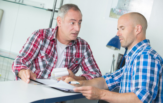 two carpenters are talking while holding papers