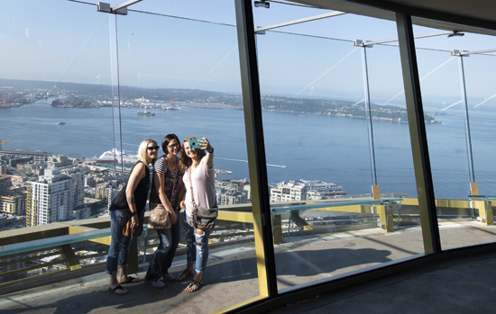 Guests take a selfie on the Space Needle's open-air observation deck, located 520-feet in the air